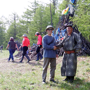 Dr. Chen shakes hands with a guide at a Mongolian heritage site.